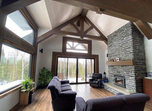 Salon avec foyer maison de bois rond